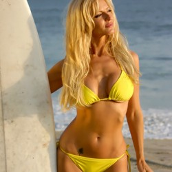 Blonde Woman holding a Surfboard in a Bikini
